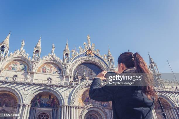 black hair female tourist taking a photograph of st mark's cathedral in piazza san marco - photo messaging stock photos and pictures
