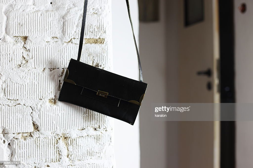 black handbag on the wall : Stock Photo