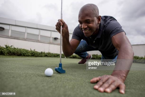 black handsome man having fun playing mini golf - miniature golf stock photos and pictures