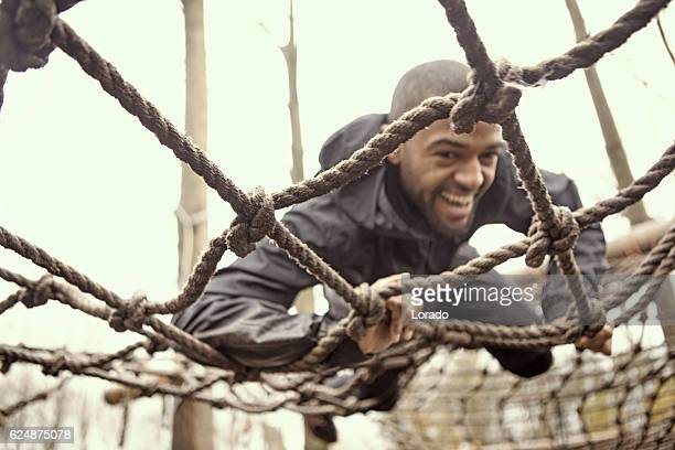 black handsome young man climbing over obstacle during mud run - obstacle course stock photos and pictures