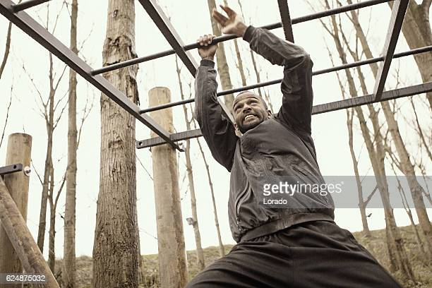 Black handsome young man climbing under obstacle during mud run