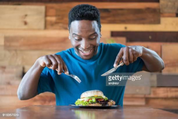 Schwarzen glücklicher Mensch hungern und Essen einen leckeren hamburger