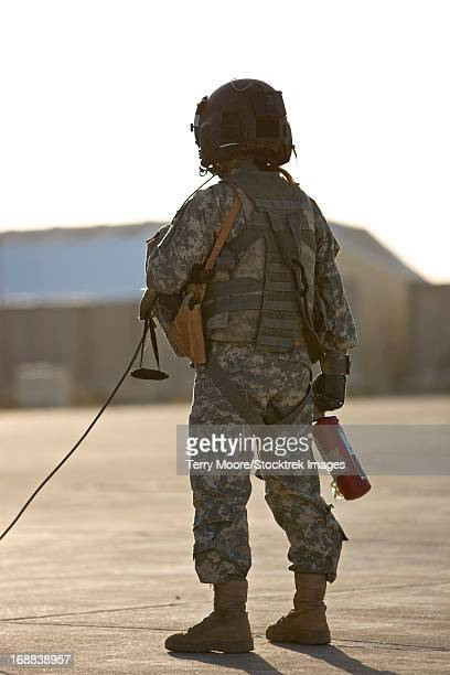 A UH-60 Black Hawk flight crew member stands by with a fire extinguisher, Tikrit, Iraq.