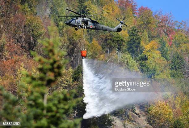 Black Hawk helicopter dumps 600 gallons of water near the peak of the 600foot high Kinsman Ridge in Woodstock NH on Oct 5 2017 A fire has burned...