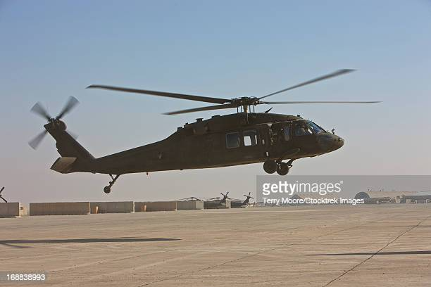 A UH-60 Black Hawk helicopter landing at a military base in Iraq.