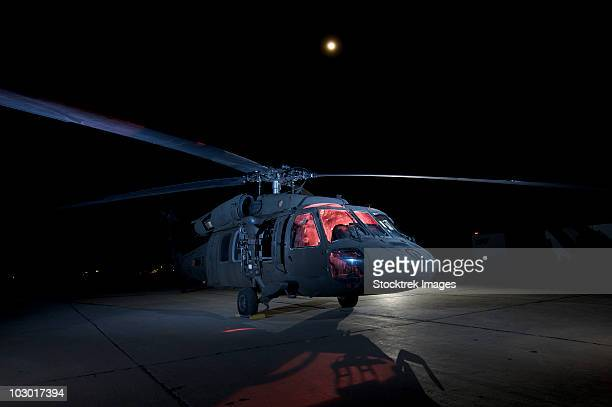 A UH-60 Black Hawk helicopter lit up by multiple flash units under a full moon.