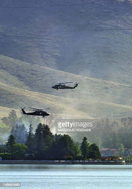 Black Hawk helicopters fly near the Spozhmai Hotel in Qargha lake in the outskirts of Kabul on June 22 2012 Taliban militants armed with guns and...