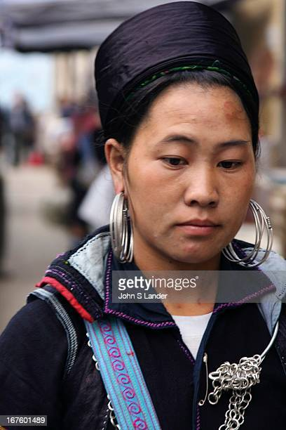Black Hmong tribal women dress in indigo clothing enormous silver earrings and black hats They are named for the dark indigo dye used in their...