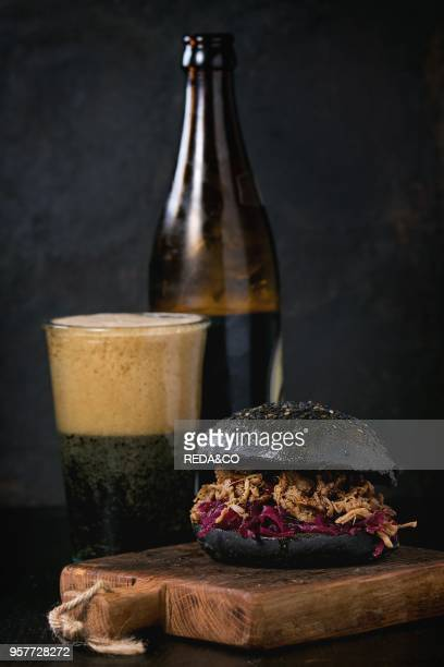 Black homemade burger with stews and red cabbage served on small wooden chopping board with glass and bottle of dark beer over wooden table with...