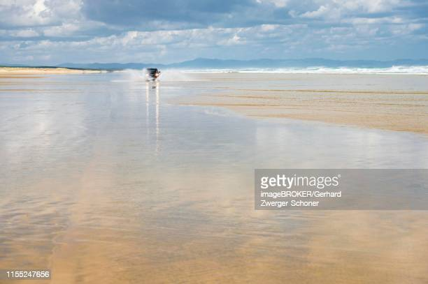 black hyundai santa fe 4x4 off-road vehicle drives on the sandy beach of ninety mile beach in the water, far north district, northland, north island, new zealand - wading stock pictures, royalty-free photos & images