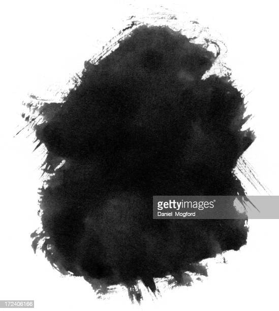 Black ink blot splattered on a white background