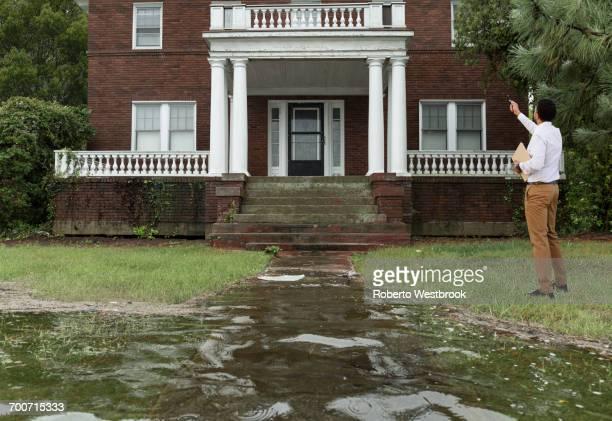 Black insurance adjuster examining flooding damage to house