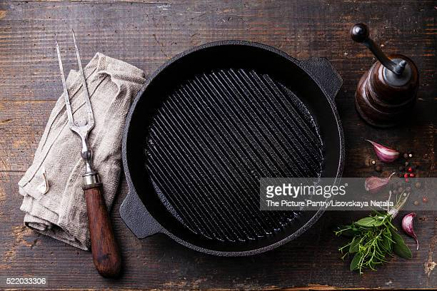 Black iron empty grill pan and meat fork on wooden texture backg