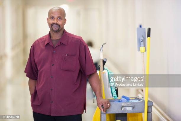 Black janitor standing with cleaning cart