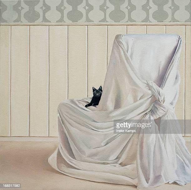 Black kitten on white chair