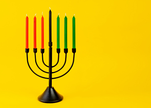 Black Kwanzaa candelabra with red, green, and black candles on yellow background. - gettyimageskorea