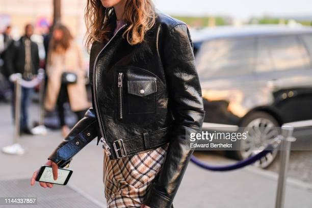 Black leather biker jacket, a camel and black checkered dress, on April 12, 2019 in Paris, France.