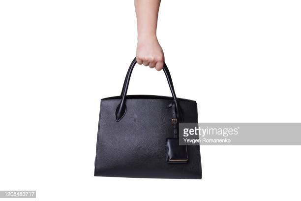 black leather handbag in women's hand on white background - brown purse stock pictures, royalty-free photos & images