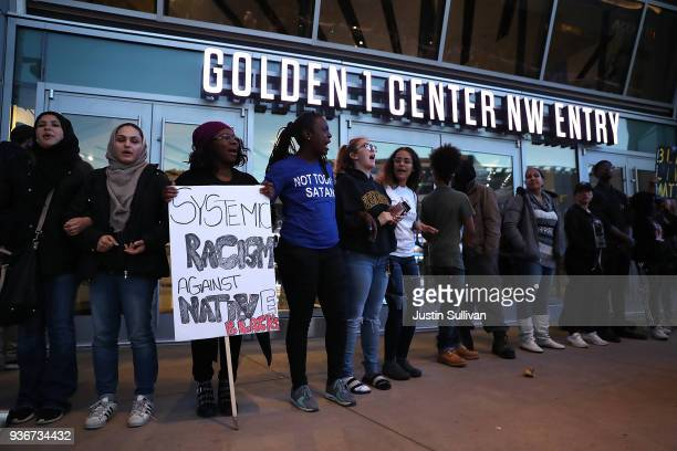 Black Live Matter protesters chant as they block the entrance to the Golden 1 Center during a demonstration on March 22 2018 in Sacramento California...