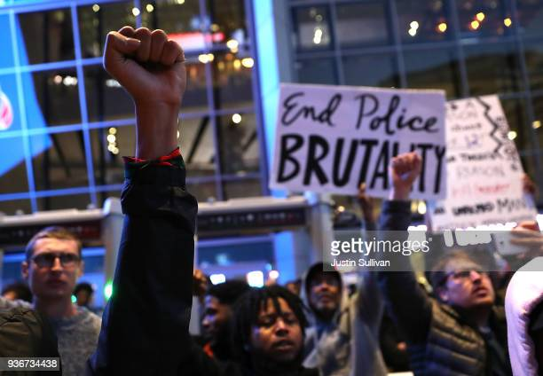 Black Live Matter protesters hold their fists in the air as they block the entrance to the Golden 1 Center during a demonstration on March 22 2018 in...