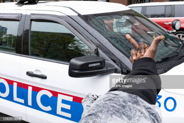 Black Lives Matter activist flips off police cruiser during the MaKhia Bryant protest in front of the Ohio Statehouse. Black Lives Matter activists...