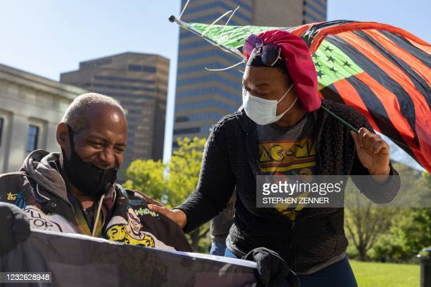 Black Lives Matter activist holds a BLM flag in his wheelchair in front of the Ohio Statehouse, with other Black Lives Matter activist connecting...