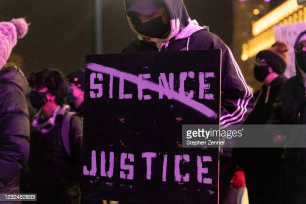 Black Lives Matter activist holds a sign against passivity in reaction to the police shooting of MaKhia Bryant on April 21, 2021 in Columbus, Ohio....