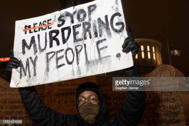 Black Lives Matter activist holds a sign against police brutality in front of the Ohio Statehouse in reaction to the shooting of Makiyah Bryant on...