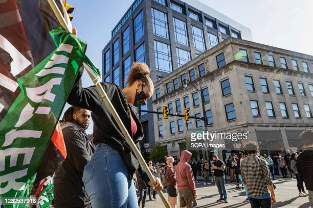 Black Lives Matter activist holds BLM flag at a protest against the police killing of Ma'Khia Bryant. Black Lives Matter activists gathered with some...