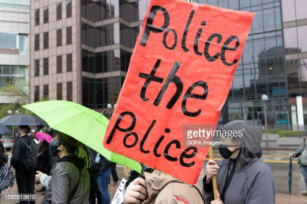 """Black Lives Matter activist holds sign reading """"police the police"""" during the MaKhia Bryant protest in front of the Ohio Statehouse. Black Lives..."""
