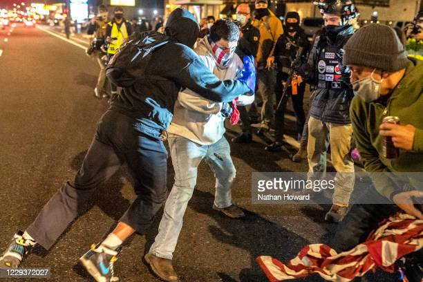 Black Lives Matter activists clash with a right-wing protester after the crowd attempted to burn an American flag on October 30, 2020 in Vancouver,...
