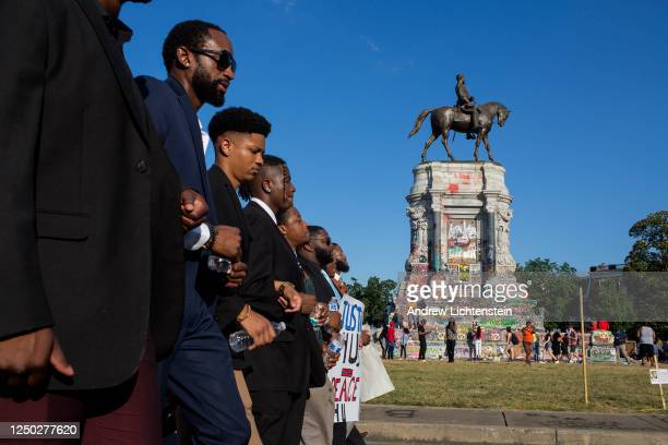 Black Lives Matter activists occupy the traffic circle underneath the statue of Confederate General Robert Lee, now covered in graffiti, on June 13,...