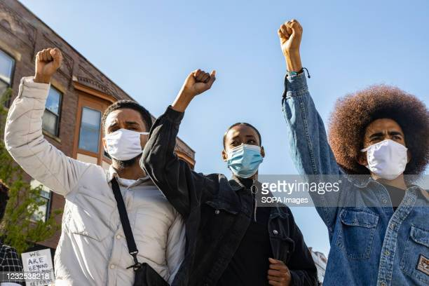 Black Lives Matter activists raise their fists in solidarity at a protest against the police killing of Ma'Khia Bryant that commandeered High St....