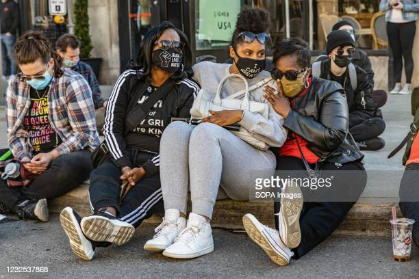 Black Lives Matter activists sit and comfort one another during 16 minutes of silence to commemoration Ma'Khia Bryant. Black Lives Matter activists...