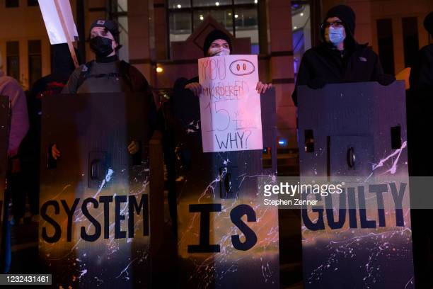 Black Lives Matter activists stand with shields outside of the Columbus Police Headquarters in reaction to the police shooting of Makiyah Bryant on...