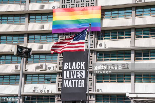 Black Lives Matter banner, a United States national flag and a rainbow flag are hung on the facade of the US embassy building in Seoul. A Black Lives...