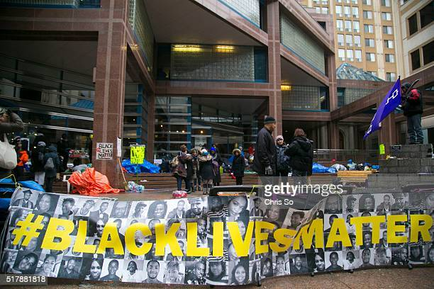 Black Lives Matter banner hangs outside Toronto Police Headquarters as protestors try to see shelter from freezing rain under the building overhang.