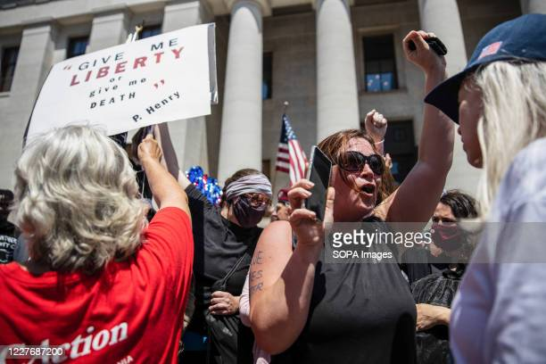 Black Lives Matter counter protester chants slogans during an 'Anti-Mask' rally, Black Lives Matter protest at Ohio Statehouse. Over 200 people...