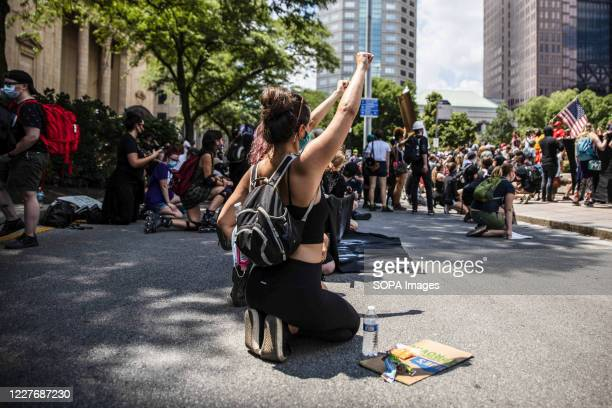 Black Lives Matter counter protester take a knee to confront the 'Anti-Mask' demonstrators during an 'Anti-Mask' rally, Black Lives Matter protest at...