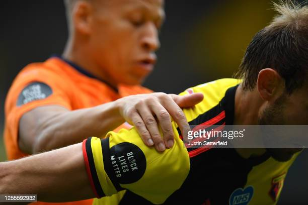 A black lives matter logo is seen on the shirt of Craig Dawson of Watford as he battles for possession with Dwight Gayle of Newcastle United during...