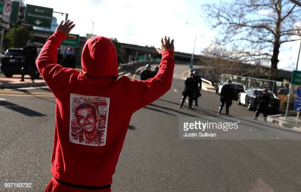 Black Lives Matter protester wears a sweatshirt with an image of Stephon Clark as he approaches California Highway Patrol officers that are blocking...