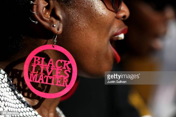 Black Lives Matter protester wears custom earrings during a demonstration outside of office of Sacramento district attorney Anne Schubert on March 28...