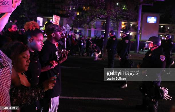 Black Lives Matter protesters confront a line of California Highway Patrol officers during a demonstration on March 30 2018 in Sacramento California...
