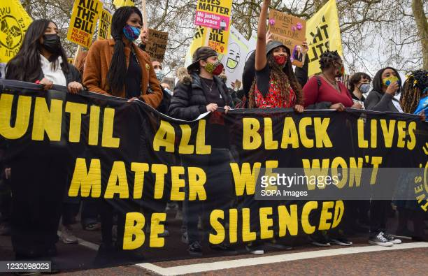Black Lives Matter protesters hold a banner as they take part during the Kill The Bill march outside Buckingham Palace. Thousands of people marched...
