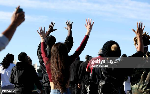 Black Lives Matter protesters hold their hands up as they march on Interstate 5 during a demonstration on March 22 2018 in Sacramento California...
