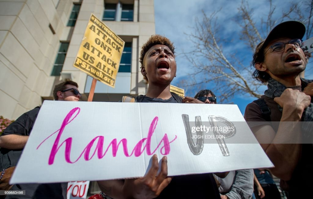 TOPSHOT - Black Lives Matter protesters march for Stephon Clark on the day of his funeral in downtown Sacramento, California on March 29, 2018. Stephon Clark, an unarmed African American, was shot and killed by police on March 18, 2018 at his grandmother's home. /