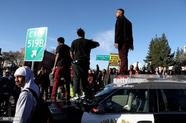 Black Lives Matter protesters stand on a California Highway Patrol car on Interstate 5 during a demonstration on March 22 2018 in Sacramento...