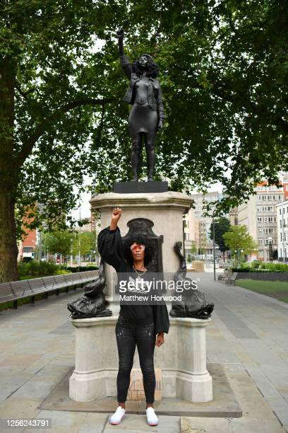 Black Lives Matter protestor Jen Reid poses for a photograph in front of a sculpture of herself by local artist Marc Quinn on the plinth where the...