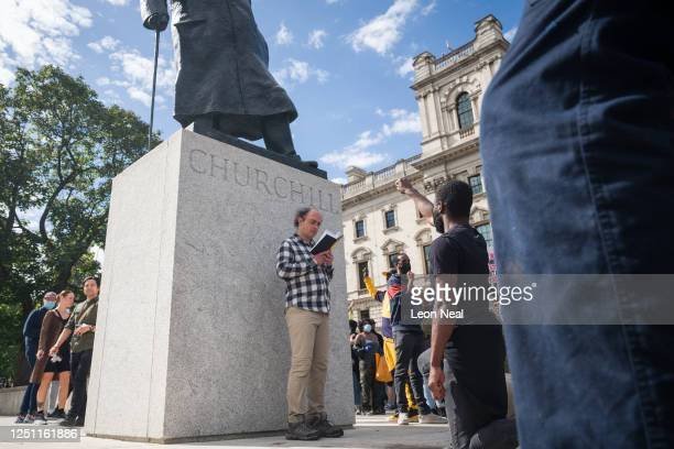 Black Lives Matter protestor takes the knee as a man makes a passive defence of a statue of Winston Churchill in Parliament Square on June 21, 2020...