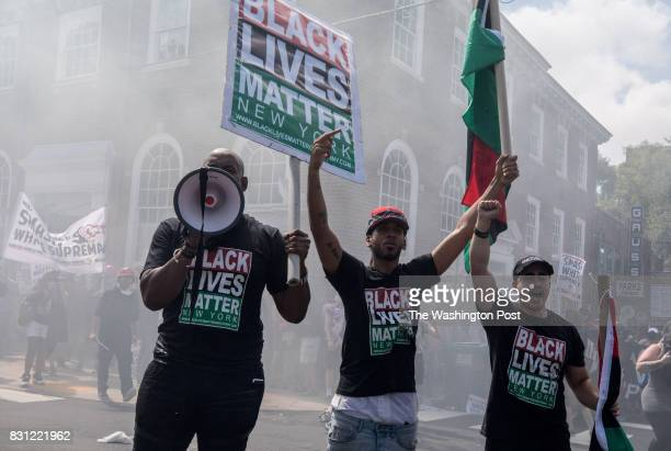 Black Lives Matter protestors stand in a fog of tear gas during clashes at the Unite the Right rally in Charlottesville VA August 12 2017